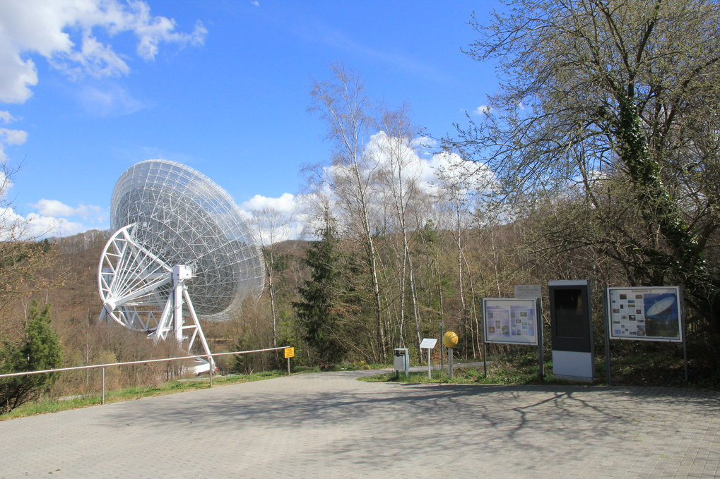 "The 100-m radio telescope seen from the courtyard of the visitors' pavilion. The yellow ball marks the station ""Sun"" of the Effelsberg Planetary Walk. This walk includes 11 stations in total: the sun, 8 planets, dwarf planet Pluto and the nearby star Sirius as transatlantic extension."