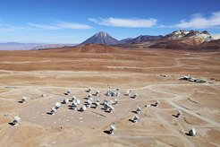 Astronomy in the desert: An aerial photograph of the Chajnantor Plateau with the antennas of the ALMA Observatory situated more than 5,000 m above sea level in the Chilean Andes. The peaks of Juriques, Cerro Toco, and Cerro Chajnantor (from left) are visible on the horizon. The photograph was taken in December 2012, three months before the official opening of ALMA.